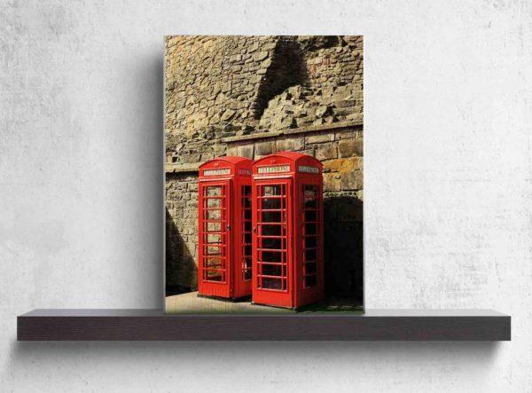 Schottland Edinburgh. Es zeigt das Bild von 2 britischen Telefonzellen, die nebeneinander vor einer grauen Natursteinwand, welche charakteristisch für Edinburgh ist, stehen. Die Telefonzellen sind in knalligem Rot. Das Holzbild ist im Hochformat und steht auf einem schwarzen Wandregal vor weißem Hintergrund.