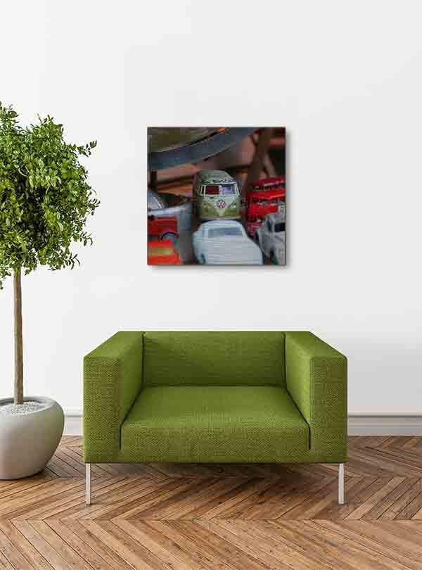 Schottland Edinburgh. Es zeigt das Bild, fotografiert in einem Antiquitätenshop, von verschiedenen historischen Spielzeugautos, darunter 2 London Bus, 1 VW Bus, 1 VW Käfer und 3 weiteren Oldtimer Autos, diese stehen unter einem Globus, von dem nur der untere Teil zu sehen ist. Das Bild ist quadratisch und in Farbe. Das Alu Dibond Bild hängt an einer stylische eingerichteten Wohnzimmerwand.