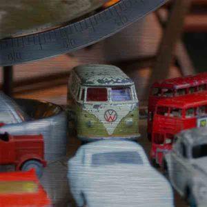 Schottland Edinburgh. Es zeigt das Bild, fotografiert in einem Antiquitätenshop, von verschiedenen historischen Spielzeugautos, darunter 2 London Bus, 1 VW Bus, 1 VW Käfer und 3 weiteren Oldtimer Autos, diese stehen unter einem Globus, von dem nur der untere Teil zu sehen ist. Das Bild ist quadratisch und in Farbe.