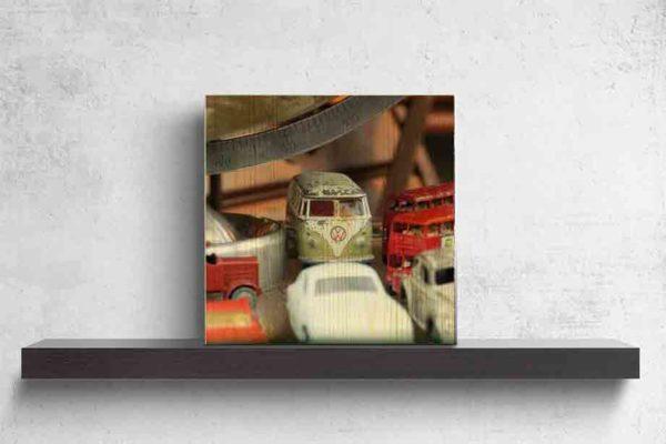 Schottland Edinburgh. Es zeigt das Bild, fotografiert in einem Antiquitätenshop, von verschiedenen historischen Spielzeugautos, darunter 2 London Bus, 1 VW Bus, 1 VW Käfer und 3 weiteren Oldtimer Autos, diese stehen unter einem Globus, von dem nur der untere Teil zu sehen ist. Das Bild ist quadratisch und in Farbe. Das Bild aus Holz steht auf einem schwarzen Wandregal vor weißem Hintergrund.
