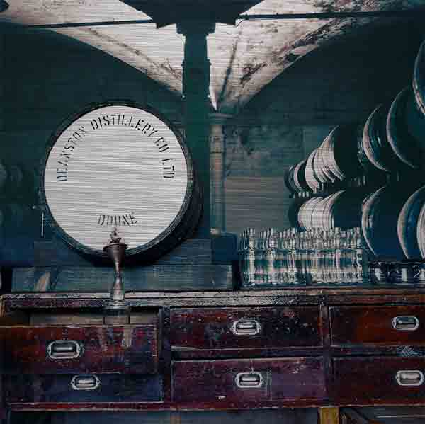 Schottland Brennerei Deanston. Es zeigt das Bild einer manuellen Whisky Abfüllung aus früheren Zeiten. Fast in der Bildmitte ist ein Whiskyfass der Brennerei Deanston, dieses steht auf einem historischen Schreibtisch, von dem 6 Schreibtischschubladen zu sehen sind. Rechts stehen kleinere Flaschen und im Hintergrund ist ein großes Wandbild mit Whiskyfässern, rechts und links des Bildes. Das Bild ist im Querformat und in Farbe.