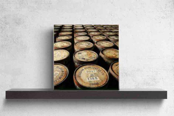 Schottland Brennerei Deanston Whiskyfässer. Es zeigt das Bild von Whiskyfässern in einer Destillerie in den schottischen Highlands. Die Holzfässer sind stehend mit dem Fassdeckel nach oben, so dass die Bezeichnung der Inhalte gut zu lesen ist. Das Bild ist quadratisch und in Farbe. Das Bild steht auf einem schwarzen Wandregal vor weißem Hintergrund.