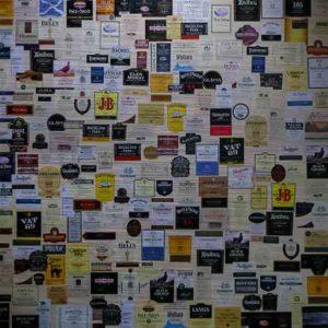 Schottland Edinburgh. Es zeigt das Bild von verschiedenen schottischen Whiskylabels, welche nebeneinander an einer Wand angebracht sind.
