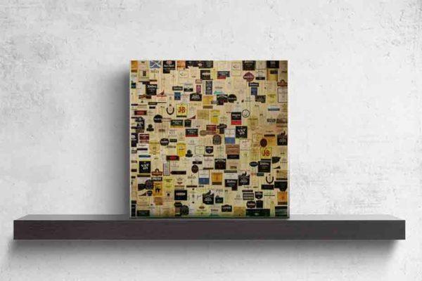 Schottland Edinburgh. Es zeigt das Bild von verschiedenen schottischen Whiskylabels, welche nebeneinander an einer Wand angebracht sind. Das Bild aus Holz steht auf einem schwarzen Wandregal vor weißem Hintergrund.