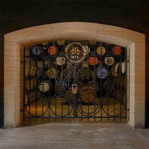"""Schottland Destillerie Glengoyne. Es zeigt das Bild von einer verschlossenen verzierten Eisentür mit einem großen Vorhängeschloss. Im oberen Teil der Tür ist das Wappen der Brennerei mit der Aufschrift """"Glengoyne Distillery No.1 – Duty Free Warehouse"""" zu sehen. Durch die Eisengitter kann man die schönen Whiskyfässer sehen. Die Deckel der Whiskyfässer haben verschiedene Farben und Aufschriften. Der Inhalt der Whiskyfässer scheint wertvoll zu sein, da diese gut gesichert ist. Das Bild ist im Querformat und in Farbe."""