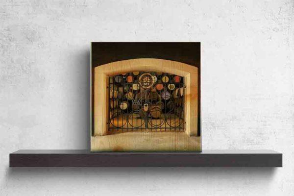 """Schottland Destillerie Glengoyne. Es zeigt das Bild von einer verschlossenen verzierten Eisentür mit einem großen Vorhängeschloss. Im oberen Teil der Tür ist das Wappen der Brennerei mit der Aufschrift """"Glengoyne Distillery No.1 – Duty Free Warehouse"""" zu sehen. Durch die Eisengitter kann man die schönen Whiskyfässer sehen. Die Deckel der Whiskyfässer haben verschiedene Farben und Aufschriften. Der Inhalt der Whiskyfässer scheint wertvoll zu sein, da diese gut gesichert ist. Das Holzbild ist quadratisch und steht auf einem schwarzen Wandregal vor weißem Hintergrund."""