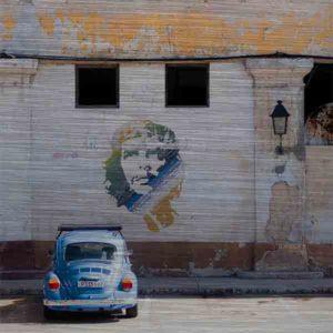 Havanna Che Guevara. Es zeigt das Bild eines VW Käfers welcher vor einem Graffiti des kubanischen Revolutionskämpfers Che Guevara geparkt ist. Das Graffiti ist auf ein leicht verfallenes typisches kubanisches Gebäude gesprüht. Der VW-Käfer hat die Farbe Blau und das Graffiti von Che Guevara ist in den Farben Blau, Grün, Gelb und Weiß. Das Gebäude hat oben 2 größere Fenster und darunter 2 kleinere Fenster. An dem Gebäude ist eine kleine Laterne angebracht. Das Alu Dibond Bild ist quadratisch