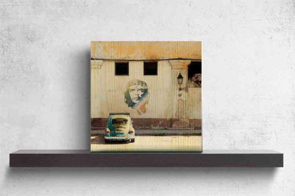 Havanna Che Guevara. . Es zeigt das Bild eines VW Käfers welcher vor einem Graffiti des kubanischen Revolutionskämpfers Che Guevara geparkt ist. Das Graffiti ist auf ein leicht verfallenes typisches kubanisches Gebäude gesprüht. Der VW-Käfer hat die Farbe Blau und das Graffiti von Che Guevara ist in den Farben Blau, Grün, Gelb und Weiß. Das Gebäude hat oben 2 größere Fenster und darunter 2 kleinere Fenster. An dem Gebäude ist eine kleine Laterne angebracht. Das Holzbild ist im Hochformat und steht und auf einem schwarzen Wandregal vor einem weißem Hintergrund.