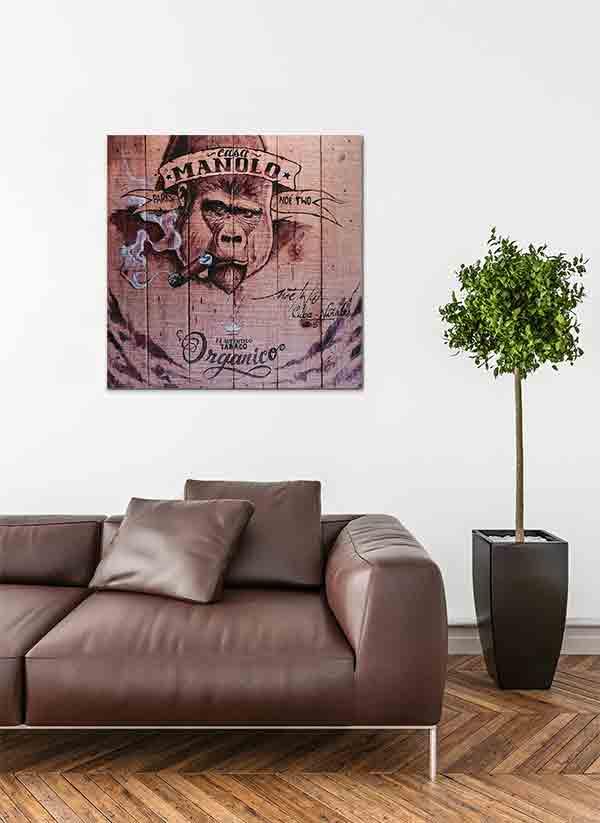 Havanna Zigarren Label. Es zeigt das Bild eines auf Holzdielen gemalten Gorillas, der eine Zigarre raucht. Auf der Stirn des Gorillas stehen die Worte Casa Manolo und weiter unten am Bild ist eine Krone gezeichnet darunter die Worte Tabaco Organico. Das Bild ist in verschiedenen hellen und dunklen Brauntönen. Rechts unten stehen noch weitere Worte in Schreibschrift. Das Alu Dibond Bild ist quadratisch und hängt an einer stylischen eingerichteten Wohnzimmerwand.