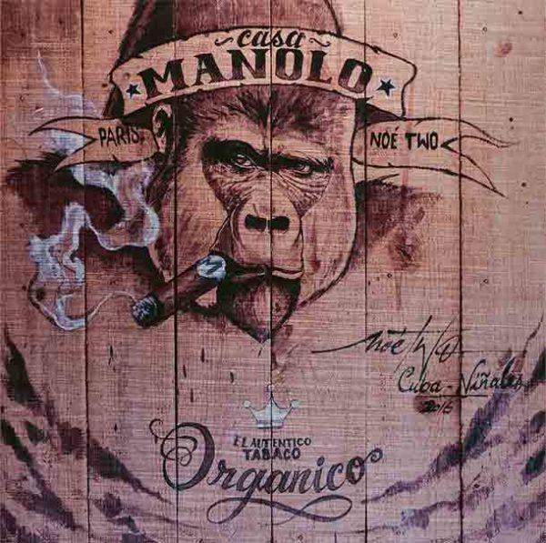 Havanna Zigarren Label. Es zeigt das Bild eines auf Holzdielen gemalten Gorillas, der eine Zigarre raucht. Auf der Stirn des Gorillas stehen die Worte Casa Manolo und weiter unten am Bild ist eine Krone gezeichnet darunter die Worte Tabaco Organico. Das Bild ist in verschiedenen hellen und dunklen Brauntönen. Rechts unten stehen noch weitere Worte in Schreibschrift. Das Alu Dibond Bild ist iquadratisch.