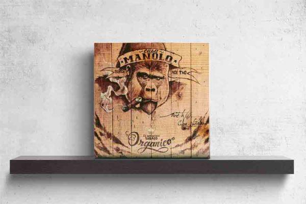 Havanna Zigarren Label. Es zeigt das Bild eines auf Holzdielen gemalten Gorillas, der eine Zigarre raucht. Auf der Stirn des Gorillas stehen die Worte Casa Manolo und weiter unten am Bild ist eine Krone gezeichnet darunter die Worte Tabaco Organico. Das Bild ist in verschiedenen hellen und dunklen Brauntönen. Rechts unten stehen noch weitere Worte in Schreibschrift. Das Holzbild ist im Querformat und steht und auf einem schwarzen Wandregal vor einem weißem Hintergrund.