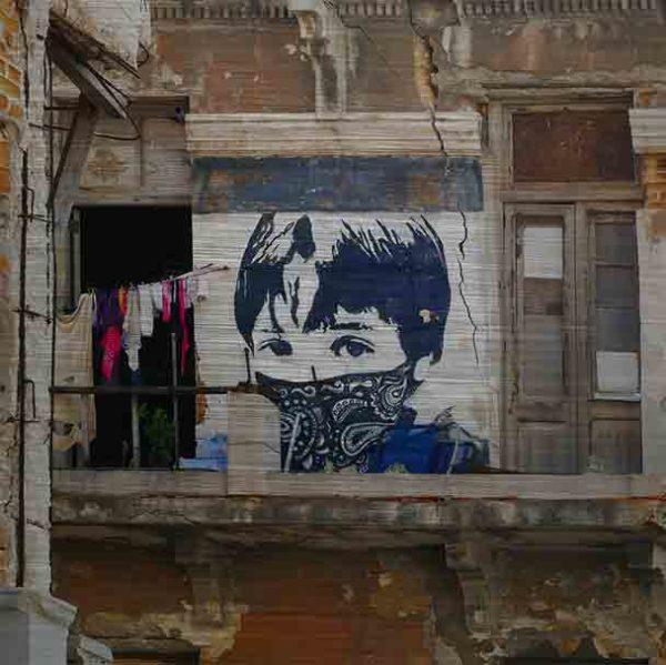 Havanna StreetArt. Es zeigt das Bild eines Graffiti's an einem Haus in Havanna. Das Haus ist ziemlich verfallen, vom Balkon ist nur noch ein Teil vorhanden. Der Balkon ist noch begehbar, jedoch ist kein Geländer angebracht. Es ist eine Wäscheleine befestigt, an der verschiedene bunte Kleidungsstücke hängen. Das StreetArt mit dem Jungen ist in verschiedenen Blau- und Weißtönen. Es ist eine Porträtaufnahme des Jungen bis zu den Schultern zu sehen, er trägt eine Kurzhaarfrisur, jedoch trägt er ein Blau-Weißes Tuch über Nase und Mund, welches an einen maskierten Guerillakämpfer erinnert. Das Alu Dibond Bild ist quadratisch.