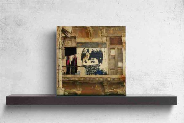 Havanna StreetArt. Es zeigt das Bild eines Graffiti's an einem Haus in Havanna. Das Haus ist ziemlich verfallen, vom Balkon ist nur noch ein Teil vorhanden. Der Balkon ist noch begehbar, jedoch ist kein Geländer angebracht. Es ist eine Wäscheleine befestigt, an der verschiedene bunte Kleidungsstücke hängen. Das StreetArt mit dem Jungen ist in verschiedenen Blau- und Weißtönen. Es ist eine Porträtaufnahme des Jungen bis zu den Schultern zu sehen, er trägt eine Kurzhaarfrisur, jedoch trägt er ein Blau-Weißes Tuch über Nase und Mund, welches an einen maskierten Guerillakämpfer erinnert. Das Holzbild ist quadratisch und steht und auf einem schwarzen Wandregal vor einem weißem Hintergrund.