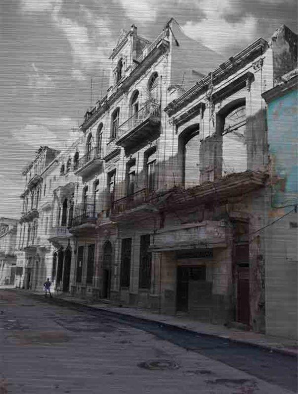 Havanna Häuser. Es zeigt das Bild einer verfallenen Häuserfassade im Kolonialstil. Von einem Teil steht nur noch die Fassade, dahinter ist kein Haus und in den Fenstern ist auch kein Fensterglas mehr. Die weiteren Häuserfronten sind auch vom Verfall geprägt, jedoch noch bewohnt. Vor den Häusern ist ein Gehsteig, auf dem weit hinten eine Person steht. Die Straße ist leer und unbefahren. Das Alu Dibond Bild ist im Hochformat.