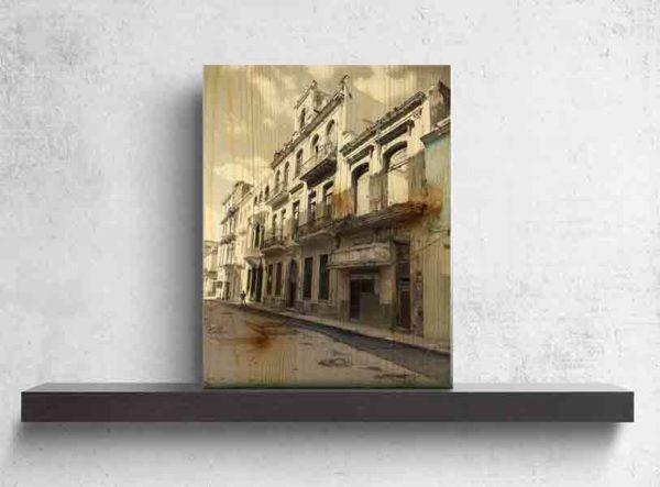 Havanna Häuser. Es zeigt das Bild einer verfallenen Häuserfassade im Kolonialstil. Von einem Teil steht nur noch die Fassade, dahinter ist kein Haus und in den Fenstern ist auch kein Fensterglas mehr. Die weiteren Häuserfronten sind auch vom Verfall geprägt, jedoch noch bewohnt. Vor den Häusern ist ein Gehsteig, auf dem weit hinten eine Person steht. Die Straße ist leer und unbefahren. Das Holzbild ist im Hochformat und steht und auf einem schwarzen Wandregal vor einem weißem Hintergrund.