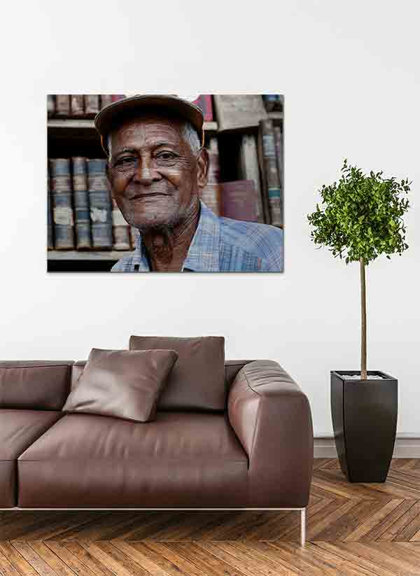 Havanna Model. Es zeigt die Porträtaufnahme eines alten Mannes aus Havanna, dessen Gesicht vom Leben gezeichnet ist. Er trägt eine Schildmütze und ein Blau/Weiß/Flieder gestreift/kariertes Herrenhemd, welches bis zur Schulter sichtbar ist. Die Hautfarbe des Mannes ist dunkel und im Hintergrund sind unscharf ältere Buchrücken zu sehen. Das Alu Dibond Bild ist im Querformat und hängt an einer stylischen eingerichteten Wohnzimmerwand.