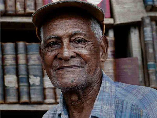 Havanna Model. Es zeigt die Porträtaufnahme eines alten Mannes aus Havanna, dessen Gesicht vom Leben gezeichnet ist. Er trägt eine Schildmütze und ein Blau/Weiß/Flieder gestreift/kariertes Herrenhemd, welches bis zur Schulter sichtbar ist. Die Hautfarbe des Mannes ist dunkel und im Hintergrund sind unscharf ältere Buchrücken zu sehen. Das Alu Dibond Bild ist im Querformat.