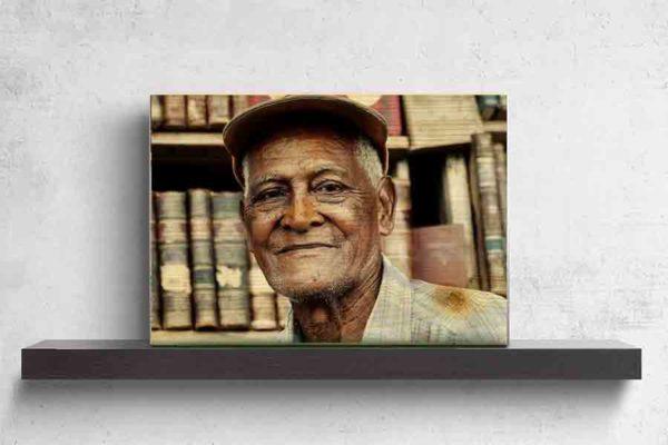 Havanna Model. Es zeigt die Porträtaufnahme eines alten Mannes aus Havanna, dessen Gesicht vom Leben gezeichnet ist. Er trägt eine Schildmütze und ein Blau/Weiß/Flieder gestreift/kariertes Herrenhemd, welches bis zur Schulter sichtbar ist. Die Hautfarbe des Mannes ist dunkel und im Hintergrund sind unscharf ältere Buchrücken zu sehen. Das Holzbild ist im Querformat und steht und auf einem schwarzen Wandregal vor einem weißem Hintergrund.