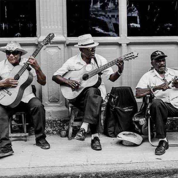 Havanna Musiker. Es zeigt das Bild von 3 dunkelhäutigen Männern, die vor einem Haus auf dem Gehweg mit ihren Stühlen sitzen und Musik machen. Zwei Männer spielen Gitarre und der andere Mann hat ein kleines Musikinstrument in den Händen. Zwei Männer tragen Hüte und ein Mann eine Baseballmütze. Alle 3 Männer sind adrett gekleidet mit einem weißen Hemd und einer dunklen Anzugshose. Im Hintergrund ist ein Haus mit Holzverkleidung und Fenstern. Das Bild ist in den Farben Schwarz-Weiß kombiniert mit Brauntönen. Das Alu Dibond Bild ist im Querformat