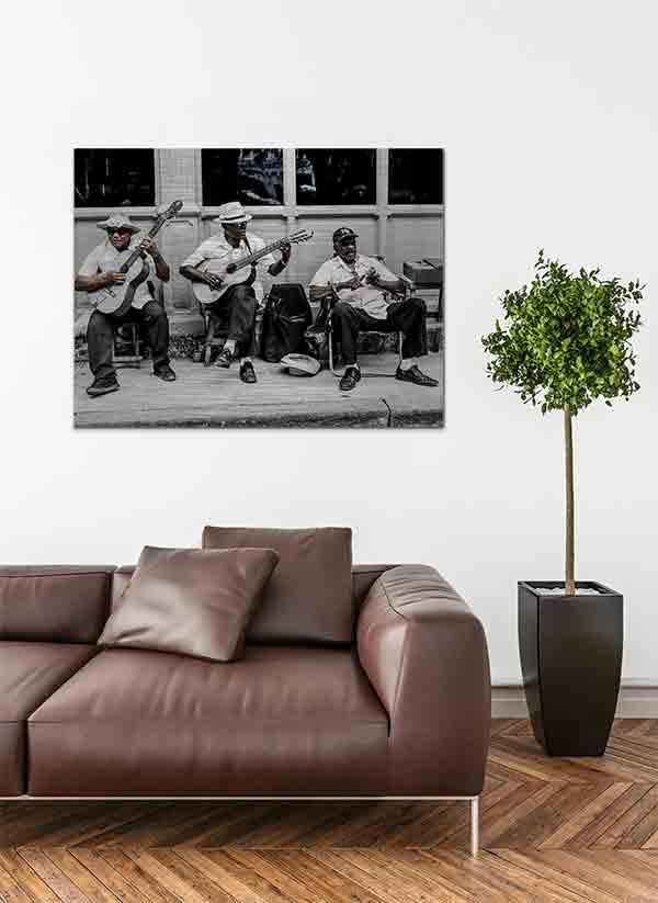Havanna Musiker. Es zeigt das Bild von 3 dunkelhäutigen Männern, die vor einem Haus auf dem Gehweg mit ihren Stühlen sitzen und Musik machen. Zwei Männer spielen Gitarre und der andere Mann hat ein kleines Musikinstrument in den Händen. Zwei Männer tragen Hüte und ein Mann eine Baseballmütze. Alle 3 Männer sind adrett gekleidet mit einem weißen Hemd und einer dunklen Anzugshose. Im Hintergrund ist ein Haus mit Holzverkleidung und Fenstern. Das Bild ist in den Farben Schwarz-Weiß kombiniert mit Brauntönen. Das Alu Dibond Bild ist im Querformat und hängt an einer stylischen eingerichteten Wohnzimmerwand.