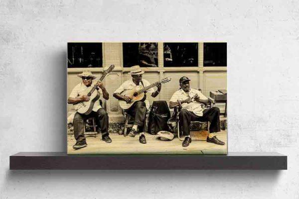 Havanna Musiker. Es zeigt das Bild von 3 dunkelhäutigen Männern, die vor einem Haus auf dem Gehweg mit ihren Stühlen sitzen und Musik machen. Zwei Männer spielen Gitarre und der andere Mann hat ein kleines Musikinstrument in den Händen. Zwei Männer tragen Hüte und ein Mann eine Baseballmütze. Alle 3 Männer sind adrett gekleidet mit einem weißen Hemd und einer dunklen Anzugshose. Im Hintergrund ist ein Haus mit Holzverkleidung und Fenstern. Das Bild ist in den Farben Schwarz-Weiß kombiniert mit Brauntönen. Das Holzbild ist im Querformat und steht und auf einem schwarzen Wandregal vor einem weißem Hintergrund.