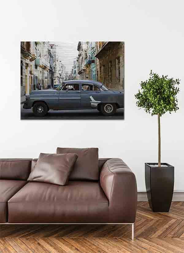 Havanna Oldtimer. Es zeigt das Bild eines amerikanischen Oldtimers der über eine Straßenkreuzung in Havanna fährt. Das Fahrzeug hat die Farbe dunkelgrau und seitlich sind Zierleisten in Chrom. Im Hintergrund des Autos verläuft eine Straße und auf beiden Straßenseiten sieht man Häuserfronten, welche teilweise schon ziemlich verfallen sind. Die Häuserfronten haben verschiedene Farben, zum Beispiel Braun, Grau, Türkis, Gelb oder Weiß. Das Alu Dibond Bild ist im Querformat und hängt an einer stylischen eingerichteten Wohnzimmerwand.
