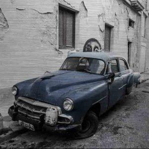 Havanna Oldtimer mit StreetArt. Es zeigt das Bild eines amerikanischen Oldtimers, welcher ziemlich verfallen in einer Seitenstraße Havannas steht. Auf der vorderen Stoßstange steht ein kleiner Benzinkanister und vor dem Fahrzeug steht noch ein größerer Benzinkanister. Zu sehen ist das linke Vorderrad, welches platt ist. Der hintere linke Fahrzeugrad fehlt komplett. Das Bild ist hauptsächlich in den Farben Schwarz/Weiß, außer der Oldtimer ist in der Farbe Blau/Lila. Das Alu Dibond Bild ist im quadratisch.