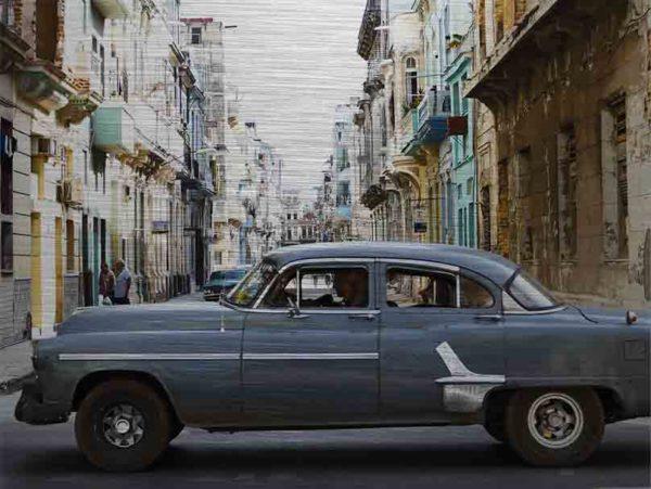 Havanna Oldtimer. Es zeigt das Bild eines amerikanischen Oldtimers der über eine Straßenkreuzung in Havanna fährt. Das Fahrzeug hat die Farbe dunkelgrau und seitlich sind Zierleisten in Chrom. Im Hintergrund des Autos verläuft eine Straße und auf beiden Straßenseiten sieht man Häuserfronten, welche teilweise schon ziemlich verfallen sind. Die Häuserfronten haben verschiedene Farben, zum Beispiel Braun, Grau, Türkis, Gelb oder Weiß. Das Alu Dibond Bild ist im Querformat.