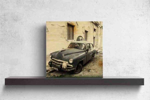 Havanna Oldtimer mit StreetArt. Es zeigt das Bild eines amerikanischen Oldtimers, welcher ziemlich verfallen in einer Seitenstraße Havannas steht. Auf der vorderen Stoßstange steht ein kleiner Benzinkanister und vor dem Fahrzeug steht noch ein größerer Benzinkanister. Zu sehen ist das linke Vorderrad, welches platt ist. Der hintere linke Fahrzeugrad fehlt komplett. Das Bild ist hauptsächlich in den Farben Schwarz/Weiß, außer der Oldtimer ist in der Farbe Blau/Lila. Das Holzbild ist im Quadratisch und steht und auf einem schwarzen Wandregal vor einem weißem Hintergrund.