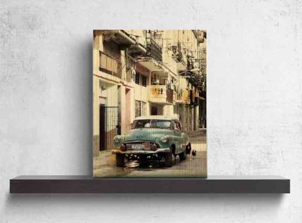 Havanna Oldtimer in Türkis. Es zeigt das Bild eines amerikanischen Oldtimers, der auf der Straße vor mehrstöckigen Stadthäusern in Havanna steht. Hinter dem Oldtimer sind 2 Hühner auf der Straße zu sehen. Der Oldtimer hat die Farbe Türkis und das Dach ist Weiß. An den Häusern habe einige Wohnungen einen Balkon und bei vielen Wohnungen ist am Balkon oder vor den Fenstern eine Wäscheleine, an der verschiedene Kleidungstücke hängen. Das Holzbild ist im Hochformat und steht und auf einem schwarzen Wandregal vor einem weißem Hintergrund..