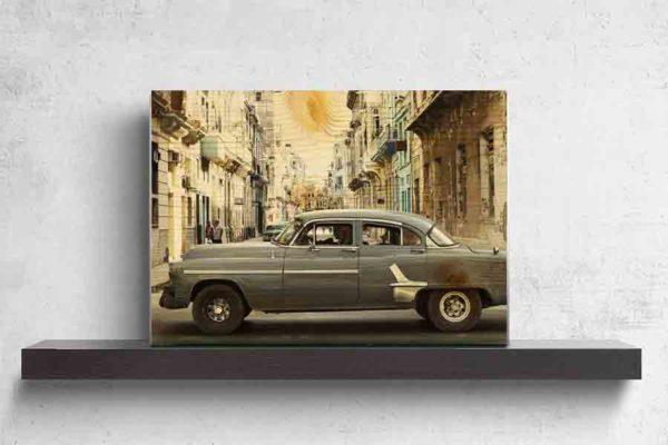 Havanna Oldtimer. Es zeigt das Bild eines amerikanischen Oldtimers der über eine Straßenkreuzung in Havanna fährt. Das Fahrzeug hat die Farbe dunkelgrau und seitlich sind Zierleisten in Chrom. Im Hintergrund des Autos verläuft eine Straße und auf beiden Straßenseiten sieht man Häuserfronten, welche teilweise schon ziemlich verfallen sind. Die Häuserfronten haben verschiedene Farben, zum Beispiel Braun, Grau, Türkis, Gelb oder Weiß. Das Holzbild ist im Querformat und steht und auf einem schwarzen Wandregal vor einem weißem Hintergrund.