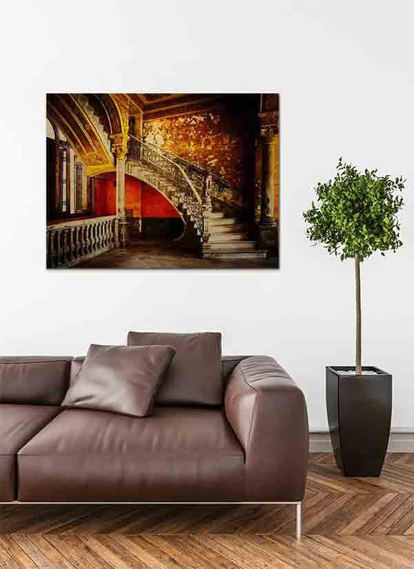Havanna Treppenaufgang. Es zeigt das Bild eines wunderschönen Treppenaufgangs in einem alten Stadthaus in Havanna. Das reichverzierte Treppengeländer schließt unten mit einer Skulptur ab, die eine Frau darstellen soll. Jedoch fehlt der Skulptur der Kopf und die Arme. Die Wände sind in den warmen Farben, Braun, Gold, Gelb, Dunkelorange und Schwarz. Die Treppenstufen sind in hellem Marmor. Im linken Bildteil ist eine weitere Säule und ein Geländer aus Naturstein darüber 2 Fenster. Das Alu Dibond Bild ist im Querformat und hängt an einer stylischen eingerichteten Wohnzimmerwand.