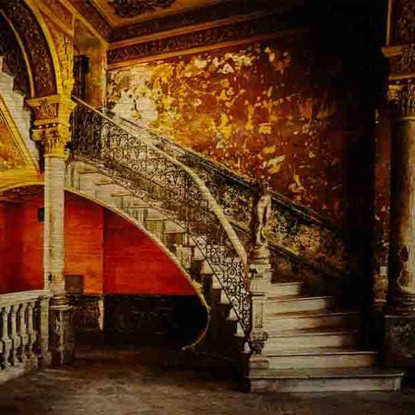 Havanna Treppenaufgang. Es zeigt das Bild eines wunderschönen Treppenaufgangs in einem alten Stadthaus in Havanna. Das prunkvolle Treppengeländer schließt unten mit einer Skulptur ab, die eine Frau darstellen soll. Jedoch fehlt der Skulptur der Kopf und die Arme. Die Wände sind in den warmen Farben, Braun, Gold, Gelb, Dunkelorange und Schwarz. Die Treppenstufen sind in hellem Marmor. Im linken Bildteil ist eine weitere Säule und ein Geländer aus Naturstein darüber 2 Fenster. Das Alu Dibond Bild ist im Querformat.