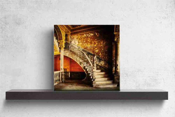 Havanna Treppenaufgang. Es zeigt das Bild eines wunderschönen Treppenaufgangs in einem alten Stadthaus in Havanna. Das reichverzierte Treppengeländer schließt unten mit einer Skulptur ab, die eine Frau darstellen soll. Jedoch fehlt der Skulptur der Kopf und die Arme. Die Wände sind in den warmen Farben, Braun, Gold, Gelb, Dunkelorange und Schwarz. Die Treppenstufen sind in hellem Marmor. Im linken Bildteil ist eine weitere Säule und ein Geländer aus Naturstein darüber 2 Fenster. Das Holzbild ist im Quadratisch und steht und auf einem schwarzen Wandregal vor einem weißem Hintergrund.