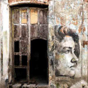 Havanna Graffiti Mädchen. Es zeigt das Bild einer Hauswand in Havanna, bei das gemalte Gesicht eines Mädchens zwischen 2 Türen abgebildet ist. Das Gesicht des Mädchens ist von der Seite abgebildet und es ist nur rechte Gesichtshälfte des Mädchens zu sehen. Die beiden Türen sind teilweise beschädigt und auch die Hauswand ist vom Verfall gezeichnet. Die Hauswand und die Türen sind in verschieden Braun- und Grautönen. Das Alu Dibond Bild ist quadratisch.
