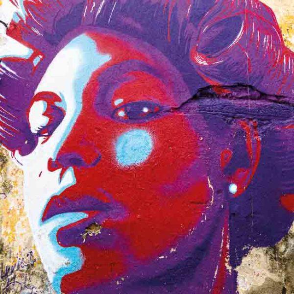 Havanna Graffiti Frau. Es zeigt das Bild eines Wandgraffitis bei dem der Kopf einer Frau abgebildet ist. Die Frau hat einen starken und stolzen Gesichtsausdruck. Der Kopf der Frau ist in den Farben Rot, Lila, Türkis und Weiss. Die Frau hat kurze Haare und in ihren Haaren sind Lockenwickler. Im Hintergrund sind noch Teile der Wand zu sehen, diese ist in den verschiedenen Brauntönen. Das Alu Dibond Bild ist quadratisch.