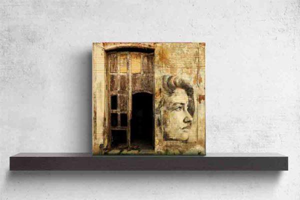 Havanna Graffiti Mädchen. Es zeigt das Bild einer Hauswand in Havanna, bei das gemalte Gesicht eines Mädchens zwischen 2 Türen abgebildet ist. Das Gesicht des Mädchens ist von der Seite abgebildet und es ist nur rechte Gesichtshälfte des Mädchens zu sehen. Die beiden Türen sind teilweise beschädigt und auch die Hauswand ist vom Verfall gezeichnet. Die Hauswand und die Türen sind in verschieden Braun- und Grautönen. Das Holzbild ist quadratisch und steht und auf einem schwarzen Wandregal vor einem weißem Hintergrund.