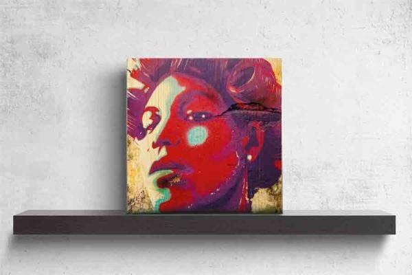 Havanna Graffiti Frau. Es zeigt das Bild eines Wandgraffitis bei dem der Kopf einer Frau abgebildet ist. Die Frau hat einen starken und stolzen Gesichtsausdruck. Der Kopf der Frau ist in den Farben Rot, Lila, Türkis und Weiss. Die Frau hat kurze Haare und in ihren Haaren sind Lockenwickler. Im Hintergrund sind noch Teile der Wand zu sehen, diese ist in den verschiedenen Brauntönen. Das Holzbild ist quadratisch und steht und auf einem schwarzen Wandregal vor einem weißem Hintergrund.